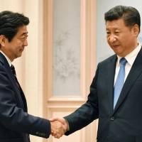 Prime Minister Shinzo Abe and Chinese President Xi Jinping get together for talks following the Group of 20 summit in Hangzhou, China, on Monday. | POOL / VIA KYODO
