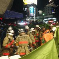 Rescue workers gather outside Seibu Railway's Takadanobaba Station in Tokyo after people on a train platform complained about a strong odor. Nine people sustained light injuries to their throats and eyes. | KYODO