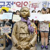 A statue symbolizing the so-called comfort women who were forced to work in Japan's wartime military brothels is seen Wednesday in front of the Japanese Embassy in Seoul.   KYODO