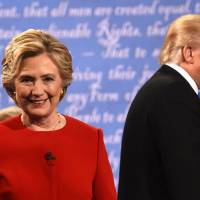 Democratic nominee Hillary Clinton and Republican nominee Donald Trump leave the stage after the first presidential debate at Hofstra University in Hempstead, New York, on Monday. | AFP-JIJI