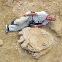 Shinobu Ishigaki, a professor at Okayama University of Science, poses besides a fossilized cast of a dinosaur footprint in Mongolia's Gobi Desert on Aug. 21. | KYODO