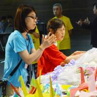 People offer flowers for the residents who were massacred in July at Tsukui Yamayuri En care facility in Sagamihara, Kanagawa Prefecture, on Wednesday during a People First gathering in Yokohama. | KYODO