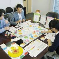 Pip Robot Technology Co. workers play a board game that simulates the costs of aging. | KYODO