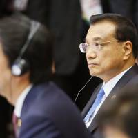Chinese Premier Li Keqiang (right) and Prime Minister Shinzo Abe listen to speeches during the ASEAN Plus Three summit in Vientiane on Wednesday. | AP