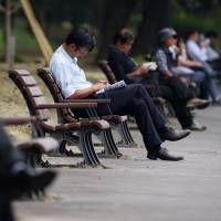 Workers rest on park benches in Tokyo in May. Two aides to Prime Minister Shinzo Abe said the nation is planning to bring in more overseas workers to bolster the shrinking labor force. | BLOOMBERG