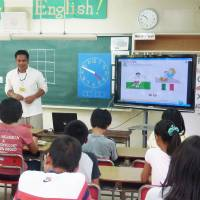 A Filipino teaches English to elementary school children in Toyonaka, Osaka Prefecture, in September 2010 as a junior high school teacher looks on. When English becomes a formal subject in elementary schools in 2020, classroom teachers, not their specialist assistants, will be tasked with conducting the lessons. | KYODO