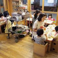 Nursery school staff have a meal with 1-year-old children on May 10 at a facility in Nagoya. | KYODO