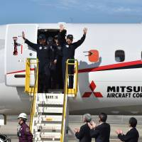 The pilots and crew of a Mitsubishi Regional Jet are welcomed by ground staff after a test flight at Nagoya Airport in Aichi Prefecture last November. | AFP-JIJI