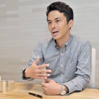 Keigo Omaki talks about his effort to document Japan's traditional craftsmen online, during an interview in Tokyo on Aug. 25. Before him is a pewter cup made by Keiichi Nakamura, one of the craftsmen featured in the video project. | YOSHIAKI MIURA