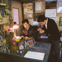 Keigo Omaki (right) observes the work of Keiichi Nakamura at the pewter craftsman's shop in Kawaguchi, Saitama Prefecture, in April. | KEIGO OMAKI