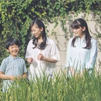 Prince Hisahito talks with his sisters, Princess Kako (center) and Princess Mako, in a rice paddy at his residence in Minato Ward, Tokyo, on Aug. 10. | IMPERIAL HOUSEHOLD AGENCY / VIA KYODO