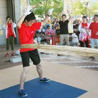 A man spins a bamboo hoop during an event in Hekinan, Aichi Prefecture, in July. | KYODO