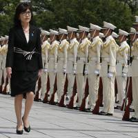 Defense Minister Tomomi Inada inspects an honor guard on her first day of work at the Defense Ministry in Tokyo on Aug. 4. | AP