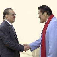 Lawmaker Kanji 'Antonio' Inoki (right) shakes hands with Ri Su Yong, North Korea's vice chairman of the Central Committee of the Worker's Party of Korea, before their meeting in Pyongyang on Saturday. | AP