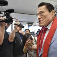 Wrestler-turned-parliamentarian Antonio Inoki speaks to the media at Beijing's international airport Thursday before flying to Pyongyang for meetings with senior North Korean officials. | KYODO