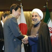 Prime Minister Shinzo Abe (left) and Iranian President Hassan Rouhani shake hands ahead of their talks in New York on Wednesday. | POOL / VIA KYODO
