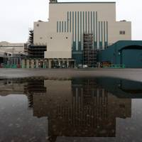 The building housing reactor 6 is reflected in a puddle outside the Kashiwazaki-Kariwa nuclear power station in Kariwa, Niigata Prefecture, in February 2015. The plant, the biggest in the world, is run by Tokyo Electric Power Co. Holdings Inc. | BLOOMBERG