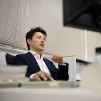 Takahiro Kusakari, chief investment officer of Sawakami Asset Management Inc., sits in front of a computer at the company's office in Tokyo on Sept. 2. | BLOOMBERG