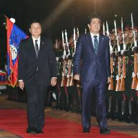 Laotian Prime Minister Thongloun Sisoulith walks with Prime Minister Shinzo Abe at a welcome ceremony in Vientiane on Tuesday. | KYODO