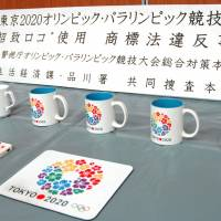 Confiscated items bearing the logo for Tokyo's campaign to host the 2020 Olympic Games are shown to the media Wednesday at Shinagawa Police Station in Tokyo. A U.S. language teacher has been arrested over suspected trademark infringement. | KYODO