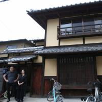 Sae Cardonnel and her French husband, Sylvain, stand in front of their traditional Kyoto 'machiya' townhouse on June 26. They restored the home with a loan from Kyoto Shinkin Bank. | REUTERS