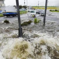Water spurts out of a manhole in Oyama, Tochigi Prefecture, on Sept. 10, 2015, following torrential rain.   KYODO