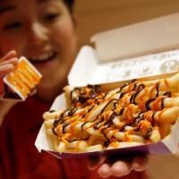 A McDonald's staff member poses with the company's 'Halloween Choco Fries' at a McDonald's restaurant in Tokyo on Thursday. | REUTERS