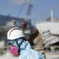 A nuclear worker passes debris at the Fukushima No. 1 plant in February. | VIA BLOOMBERG