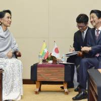 Prime Minister Shinzo Abe and Myanmar's de facto leader, Aung San Suu Kyi, hold talks in Vientiane on Wednesday. | KYODO