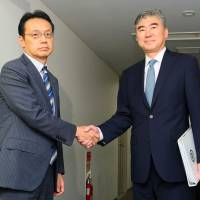 Sung Kim (right), U.S. special representative for North Korea policy, and Kenji Kanasugi, director-general of the Foreign Ministry's Asian and Oceanian Affairs Bureau, shake hands before they held talks on coordinating steps against North Korea in Tokyo on Sunday. | POOL / VIA KYODO