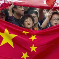 Chinese demonstrators hold national flags while marching on a street during a protest against Japan in Chengdu, China, in September 2012. | AP