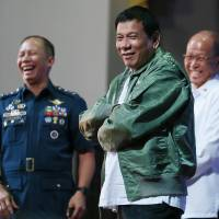 Philippine President Rodrigo Duterte wears a pilot's jacket that was presented to him on the anniversary of the 250th Presidential Airlift Wing on Tuesday at the Philippine Air Force headquarters in suburban Pasay city, southeast of Manila, Philippines. On Monday, President Duterte, in his first public statement opposing the presence of American troops, said he wants U.S. forces out of his country's south. | AP