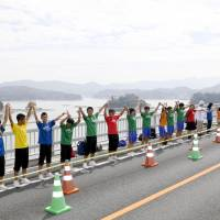 Participants taking part in a pinky swearing event held in the Amakusa area of Kumamoto Prefecture on Sunday raise their arms with their little fingers entwined. | KYODO