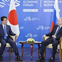 Prime Minister Shinzo Abe and Russian President Vladimir Putin pose during their meeting in Vladivostok, Russia, on Friday. The pair were focusing on economic relations and the long-running dispute over four Russian-held islands off Hokkaido. | KYODO