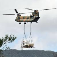 A Ground Self-Defense Force helicopter transports a truck over the village of Higashi, Okinawa Prefecture, on Tuesday. | KYODO