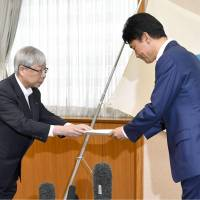 Kyushu Electric Power Co. President Michiaki Uriu (left) hands a formal reply to Kagoshima Gov. Satoshi Mitazono on Monday, rejecting his request to immediately suspend operations of two reactors at its Sendai power plant. | KYODO