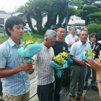 Fisherman Hisao Hashimoto (second from left) and other anti-nuclear protesters sued by Chugoku Electric Power Co. receive bouquets from supporters after settling with the utility on Aug. 30 in the city of Yamaguchi. | KYODO
