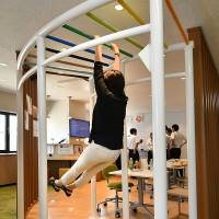A Fujikura Inc. worker swings from bars during a lunch break at the company's office in Tokyo's Koto Ward. | KYODO
