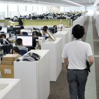At this NTT Software Corp. office in Yokohama, dividing walls have been removed to create an aisle that encourages mingling. | KYODO