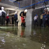 Journalists look at a pool of water in the basement of one of main complexes at the relocation site for the Tsukiji fish market in Tokyo's Koto Ward on Friday. | REIJI YOSHIDA