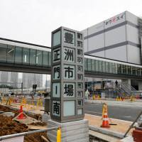 A sign reading 'Tokyo Metropolitan Central Wholesale Market, Toyosu Market, main gate — south' stands at the construction site in the Toyosu district on Monday. | REUTERS