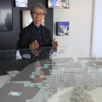 Japanese architect Riken Yamamoto explains his work for the The Circle, a mixed-use complex under construction at Zurich Airport, last month. | KYODO