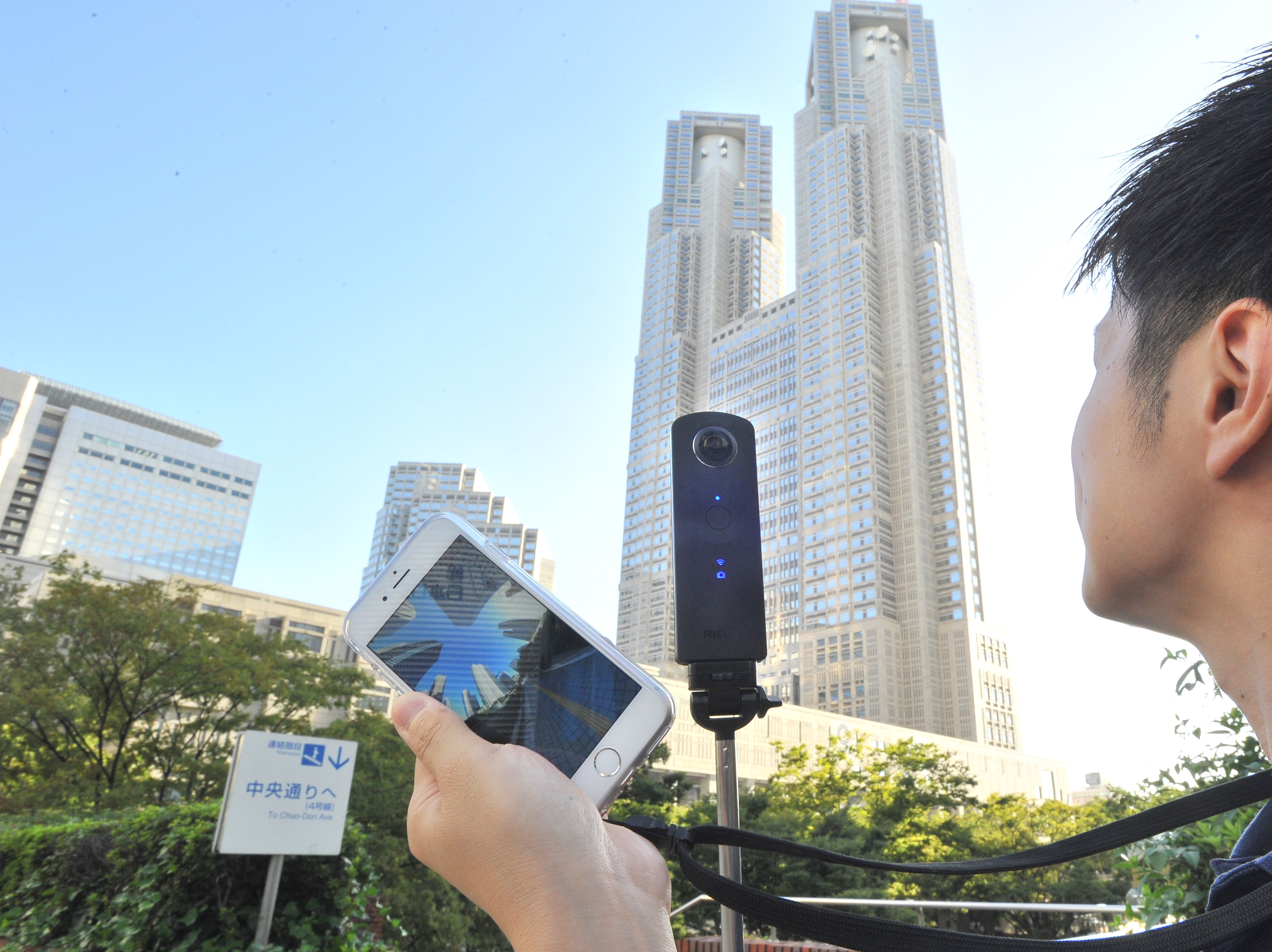 A Ricoh Theta S camera (mounted on stick) is used to take 360-degree photos near the Tokyo Metropolitan Government building in Shinjuku Ward on Aug. 31. The image can be transmitted to a smartphone for viewing. | YOSHIAKI MIURA
