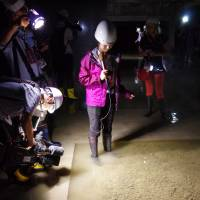 Journalists examine a flooded basement at a facility built to house the relocated Tsukiji fish market in Tokyo's Koto Ward on Friday. Local assembly members suspect that groundwater has welled up, potentially bringing toxic chemicals from contaminated land beneath. | REIJI YOSHIDA