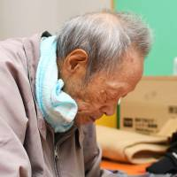 An exhausted elderly man takes a rest at an evacuation center Tuesday in the town of Iwaizumi, Iwate Prefecture. | KYODO