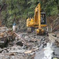 Workers restore a road that was damaged by Typhoon Lionrock on Tuesday in the town of Iwaizumi, Iwate Prefecture. | KYODO