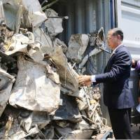 Officials inspect scrap to be returned to Japan at a port in central Thailand in July. | THAILAND'S MINISTRY OF INDUSTRY / VIA KYODO