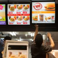 Going down?: An employee changes a sign at a McDonald's in Tokyo after prices were cut in 2014. Since then, more discounts have been added to its menu. | BLOOMBERG