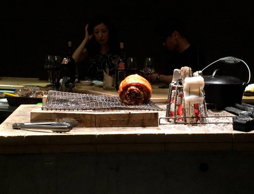 Center of attention: Porchetta (rolled pork) slowly cooks over the charcoal grill that acts as the centerpiece of the open kitchen at Falo. Customers sit at the wooden counter that runs along all four sides. | ROBBIE SWINNERTON