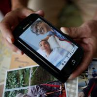 Survivor: Takashi Ono shows a recent photo of his wife, Chikiko, and stepson, Kazuya, a resident of the Tsukui Yamayuri En facility in Sagamihara. Kazuya is recovering from multiple stab  wounds that left him in critical condition after the attack at the home for people with disabilities in July.   REUTERS